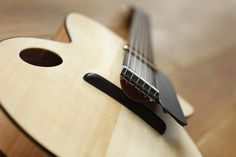 NK Forster is a maker in England making some archtops with a very unique tailpiece. Typically, an archtop's strings would pass over a bridge which is the main component that transmits the st…
