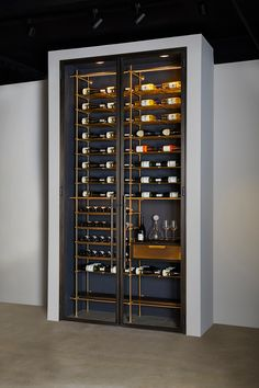 Featuring our Frankford Panel Doors and Collector's Shelving, this Wine Unit showcases Bronze double doors holding clear, low-iron tempered insulated Glass and Frankford Machined Bronze Pulls. With Lateral + Frame Collector's Shelving which allows a 150 bottle capacity, you will certainly never run dry. The Bronze Wine Room features an Oxidized Oak Sommelier Station with a Warm Brass Clad drawer face and Collector's Style Pull, as well as a carved depression for accessories. #interiordesignideas Glass Wine Cellar, Home Wine Cellars, Wine Cellar Design, Wine Shelves, Wine Storage, Shelving, Modern Home Bar, Wine Wall, Wine Racks For Wall