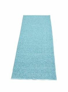The stylish plastic rug Svea from Pappelina is solid colored, woven with a mixture of solid and metallic colors in azur blue.