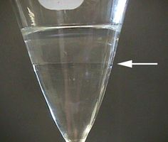 When two immiscible liquids are placed in a separatory funnel, two layers are seen. The denser solvent will be the bottom layer. Most halogenated solvents are denser than water, most non-halogenated solvents are less dense than water. If you are not sure which layer is which, add a drop of water and see which layer it joins.