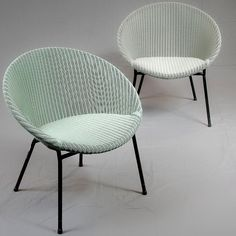 A pair of Lloyd Loom lusty lounge chairs ca. 1958. Made of basket weave wicker material, model M300 with conical configuration and black tubular