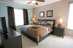 Pleasant bedroom with dark furniture that has dark curtains, dark frame queen size bed and dark cabins with two beige lamps. Also two paintings and two tone walls , turquoise and light brown colors.