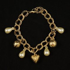 Pearl Drop Charm Bracelet:This charming charm bracelet is a vintage dead stock item. The gold bracelet measure 8 inches and features faux pearl drops, round gold charms and a beautiful gold heart in the middle. Lightweight and easy to wear for day to evening looks! $16.00