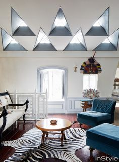 Christian Louboutin's Stunning Parisian Apartment living room with blue accent chairs and zebra rug