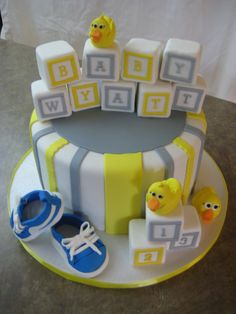 Baby Boy Shower Themes | Yellow and Gray Baby Shower Cake with Fondant Covered Blocks | Byrdie ...