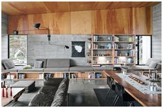 Plywood built-ins below bench. Board formed concrete walls same height as windows. Plywood walls and ceiling above.
