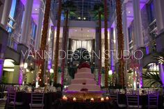 a #white four-tier cake adorned with #flowers and surrounded by #candles
