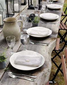 the perfect table setting for summer, lanterns, linen napkins, candles, & crockery, white plates..gray wood table, black french cafe chairs,