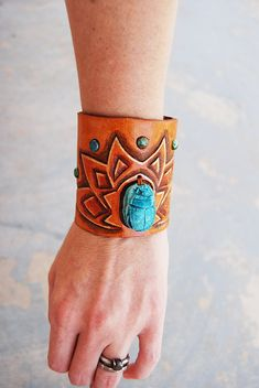 This cuff bracelet is limited edition and there are only two. Each one is hand tooled with a lotus flower, inlaid with turquoise and features a