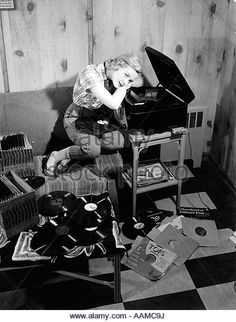 1950s TEEN GIRL LISTENING TO MUSIC ON PHONOGRAPH SIT ON COUCH LEAN ON RECORD PLAYER DREAMING RECORDS 78s - Stock Image