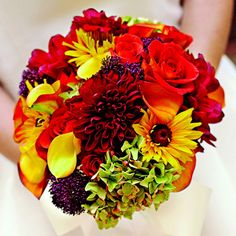 Pick a Vibrant Bouquet    The bold colors of late summer and fall make this round bouquet glow. It includes dark red dahlias, golden black-eyed Susans, yellow and orange calla lilies, purple trachelium, and orange roses. Green hydrangea blossoms fill in while preventing the colors from becoming too intense.