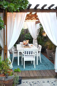 AFTER: our outdoor pergola / deck with outdoor curtains and rug, table, twinkle lights, plants  and table settings