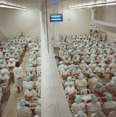 Yto Barrada Prawn processing plant in the Free Trade Zone Tangier 1998  photograph of a room of factory workers wearing green caps and white  overalls f8191d7d088c