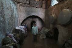 A child refugee from Kvromh village poses inside a makeshift house in the Serjilla archaeological site of Jabal al-Zawiya March 29, 2014. REUTERS/Khalil Ashawi