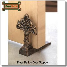 Fleur De Lis Door Stopper - Let the fresh air in with this stylish door stopper! Made from cast iron, the decorative fleur-de-lis will be a decorative delight in any room.