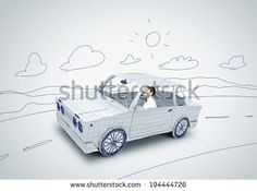 Young man driving car made of sheet of paper