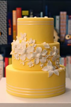 Yellow and white wedding cake by Eat Cake Be Merry.  White flowers mimic ceramic flowers with button centers. #weddingcake #yellow