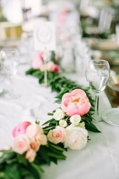 Instead of traditional wedding centerpieces, decorate reception tables with peony and rose garlands