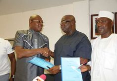 Stephen Keshi receives his new contract from Seyi Akinwunmi