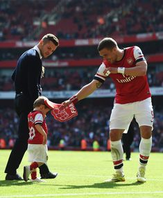 Lukas Podolski of Arsenal jokes with Jack Wilshere and his son Archie during the Barclays Premier League match between Arsenal and West Bromwich Albion at the Emirates Stadium on May 2014 in London, England. Arsenal Fc, Arsenal Football Team, Arsenal Pictures, Lukas Podolski, Jack Wilshere, Soccer Inspiration, West Bromwich, World Football, Sports