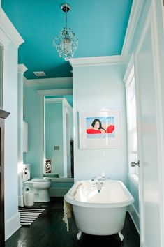 Stunning bathroom with crystal chandelier hung from turquoise ceilings over aqua blue walls