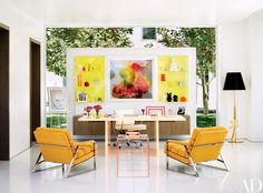 Alexandra von Furstenberg created the acrylic desk, side table, and (in collaboration with Dax Design) shelving for her Los Angeles home office, which is also outfitted with two Milo Baughman lounge chairs, an Eames desk chair by Herman Miller, a Dax Design cabinet, and a Philippe Starck floor lamp by Flos; the large photograph is by Kim Keever, and the easel displays an issue of Interview magazine signed by Andy Warhol to Von Furstenberg.