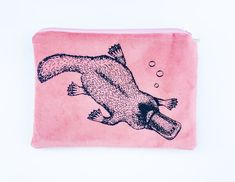 This cute soft pink platypus purse is a super handy size, the perfect purse if you're travelling light, or a super handbag organiser or makeup / pencil case.   Designed, printed and made in Tasmania by Stalley Textiles, this adorable platypus is Stalley's original design, screen printed (by her!) on soft pink fabric front, with a soft grey vegan leather reverse, fully lined and finished with a quality matching YKK zipper. #australiangifts #australiansouvenirs  www.stylishaustraliana.com.au Australian Gifts, Platypus, Unique Plants, Handbag Organization, Travel Light, Pink Fabric, Textile Artists, Tasmania, Crafts To Sell
