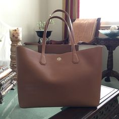 """Tory Burch Perry Tote NWT  Authentic Tory Burch Perry Tote in the bark color with gold interior. Smooth buttery pebbled leather material with resin backing, open top (no closure or magnetic closure), can easily fit a 15"""" laptop and a pair of shoes. Flat leather handles with 9.4"""" drop and interior hanging pockets with 2 pockets. Lightweight bag and easy to carry. BRAND NEW NEVER USED WITH TAGS! Dust bag, gift bag and shopping tote bag all included!    No trades or Paypal ✅ Bundles are welcome…"""