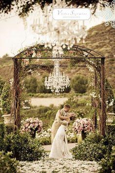 chandeliers above isle lit for night wedding.
