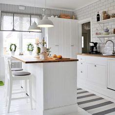 <span>Mysigt lantkök med en vit helkaklad vägg och en vägg i gråmålad träspont. Barstolar från Ikea. Matta från Hornbach. Hissgardiner och lampor från Ellos.</span>