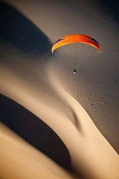 paraglider exploring newly discovered sand dune in Mozambique