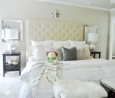 neutral-master-bedroom-with-tufted-headboard-and-lamps-and-mirrors-on-either-side-of-bed