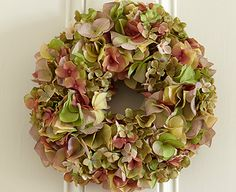 This wreath of silk hydrangea can be hung on a door or a cupboard or used flat as a candle surround