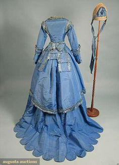 BLUE SILK FAILLE VISITING DRESS & BONNET, c. 1870 - BACK VIEW   5 pieces, most trimmed w/ box pleated & fringed self fabric: short bodice w/ long sleeves, trained skirt w/ scalloped edge, overskirt & bow back belt w/ fringed trim, woven straw & blue faille spoon bonnet, all pieces lined w/ cream cotton or buckram.