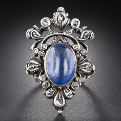 Usted se sentirá como un rey cuando usted no este anillo de zafiro y diamantes impresionante y llamativo formado como un cabujón de zafiro azul majestuosamente coronada. Rose-corte diamantes brillan de ajustes de plata, un vástago del anillo de desplazamiento bellamente perforado envuelve alrededor del dedo, y un medallón sorpresa se esconde detrás de la brillante zafiro 6,75 quilates, accesible sólo desde el totalmente grabado en el interior del anillo. Este majestuoso anillo de zafiro…