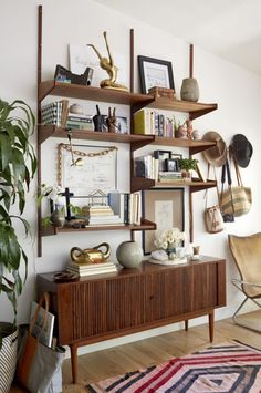 Midcentury modern wooden bookshelf with wall art and worldly decorations