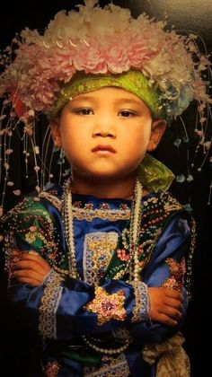 Flowers: portrait of young Shan tribe boy, undergoing a male rite of passage in northern Thailand by Kenneth Bamberg