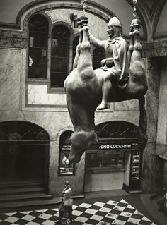 This is a photograph by Croatian photographer Stanko Abadžić. The sculpture is Svaty Vaclav (Saint Wenceslas) by Czech sculptor David Cerny. It is located at the Lucerna Palace, Switzerland.