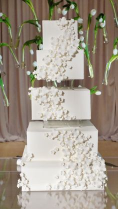 Five tiered white brides wedding cake with floating tiers and floating white tulips behind cake at summer wedding - Photos by Jenny & Eddie
