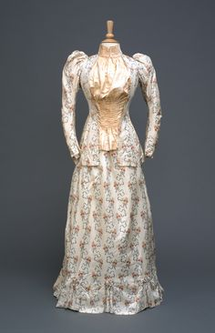 1895 Madame Clapham day dress. Long sleeves, cream silk printed with blue ribbons and pink flowers, peach silk pleated panel at front, leg of mutton sleeves, high stiff collar, long basques. Skirt, is cream with floral sprigs and blue ribbon details.