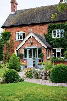 crimson brick farmhouse with massive central porch, white coving and light-weight blue entrance door brick cottage