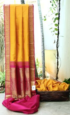 A TRADITIONAL YELLOW BROCADE KANCHIVARAM SAREE IS ENHANCED WITH A COMPLEMENTING MAGENTA AND ZARI PALLU AND BORDER