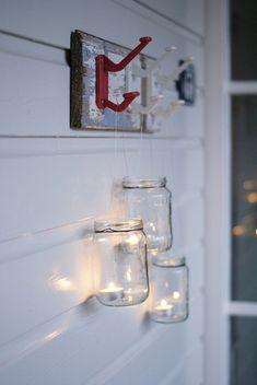 Frascos de vidrio con velas tea light en el interior colgados desde un perchero.