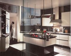 Black and white 1980s kitchen. A very regimented, clinical feel. Geometric shapes are frequent within the design, rather than flowing, natural forms.