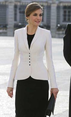 La Reina, con el pelo recogido, ha elegido un elegante vestido negro conjuntado con un blazer en color blanco