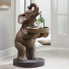 "Elephant Butler Table $139.00 $20.00 per month Ginnys Elephants have been photographed in the wild standing on hind feet to reach a high tree branch to munch on leaves. This pachyderm, however, rises to offer you a snack on its oval tray, hold a drink for a guest, or provide a spot to keep your keys. Crafted of resin to mimic hand-carved wood, it makes a unique accent table that's sure to be the talk of all who see it. Resin. 13"" w x 27"" h x 17 1/2"" d."