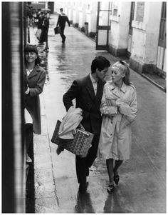 Nino Castelnuovo and Catherine Deneuve walk down a wet sidewalk in a scene from the film 'The Umbrellas Of Cherbourg', 1964. (Photo by Landa...