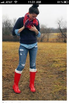 blue pull over with button up underneath, jeans and red hunter boots