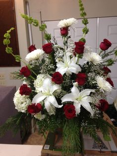 Fresh church arrangement using bells of Ireland, white lilies, white hydrangeas, white spider mums and red roses with some mixed winter greens for the beginning of the Christmas season. First Baptist Church-- November 29, 2015. Southern Traditions-- Booneville, MS--662-728-1876. Designer Matt Rinehart