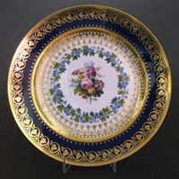 A Fine Sevres Porcelain Plate, Louis XVIII Period Dated 1821. The Center Decorated with Garden Flowers Surrounded by a Flowering Wreath. The Deep Blue Ground Border is Gilded in the Neo-Greek Style. The Base with a Printed Interlaced LLs Mark with 21 for the Date of 1821, Further Painted Marks, Probably for 21 St May 1821 as well as Incised Marks Close to the Footrim. R and G McPherson dealers in antique Chinese porcelain.